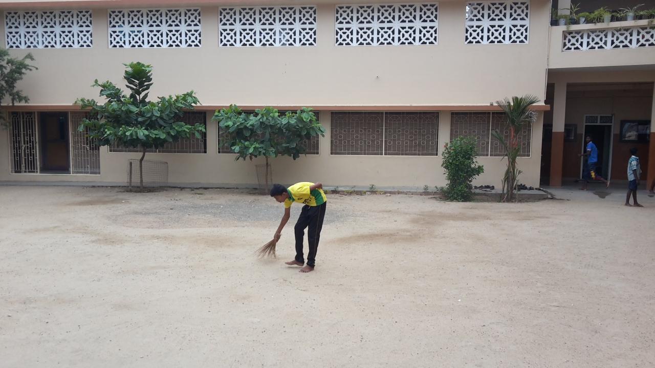 Ein Kind putzt den Hof